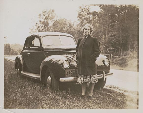 Photo noir et blanc d'une femme vêtue d'un manteau, debout devant sa voiture en bordure de la route.