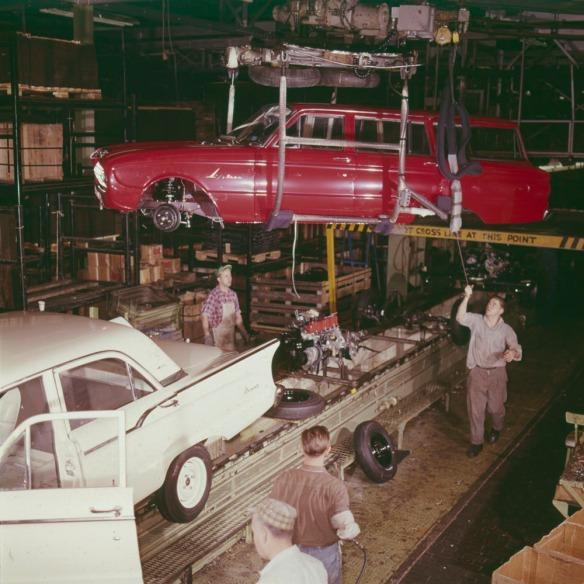 Photo couleur de deux hommes guidant la carrosserie d'une voiture familiale rouge sur une ligne de production en mouvement.