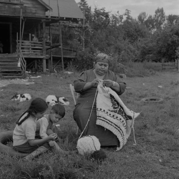 Photo noir et blanc d'une femme assise à l'extérieur, qui tricote un chandail traditionnel Cowichan. Deux enfants (un garçon et une fille) sont assis dans l'herbe à ses pieds.