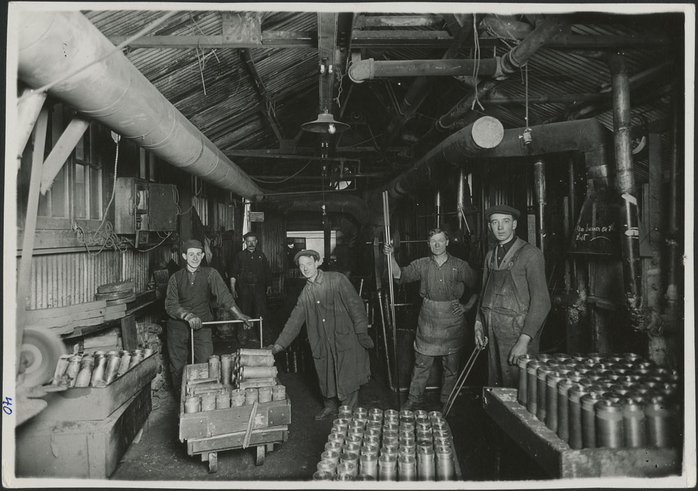 Photographie noir et blanc montrant des ouvriers debout près de centaines de cylindres d'obus.