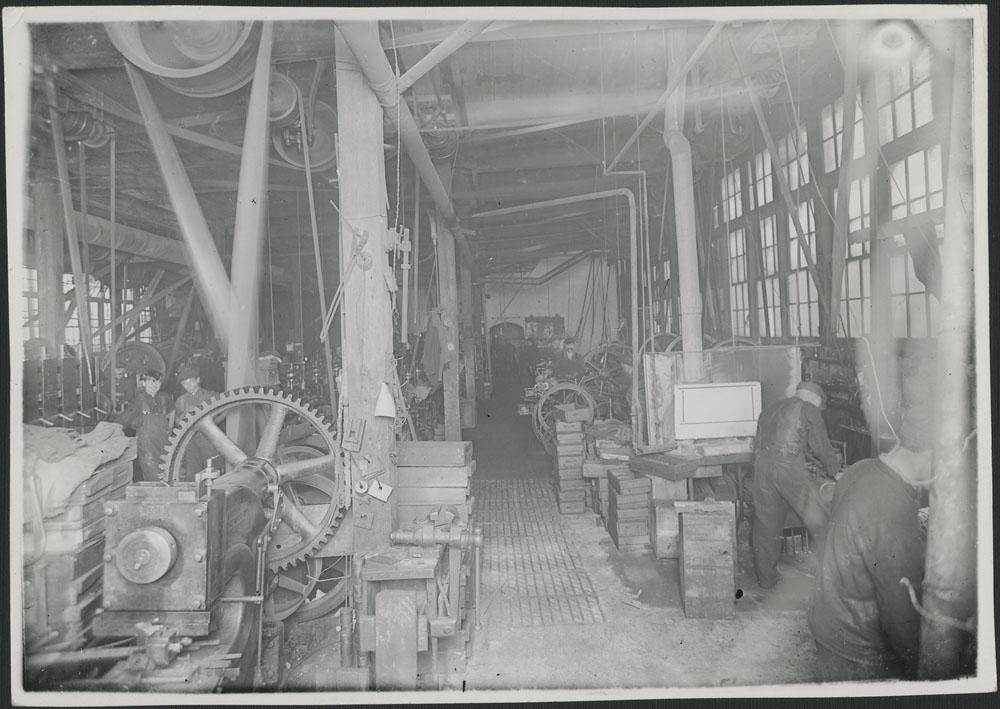 Photographie noir et blanc montrant l'intérieur d'une usine de fabrication de munitions et de fils barbelés, en 1916.