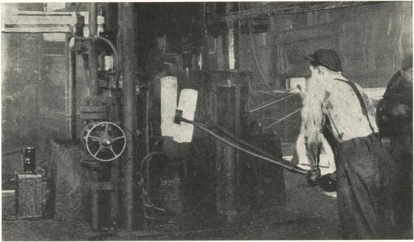 Photographie noir et blanc montrant un ouvrier manipulant un lingot d'acier brûlant à l'aide de longues pinces.