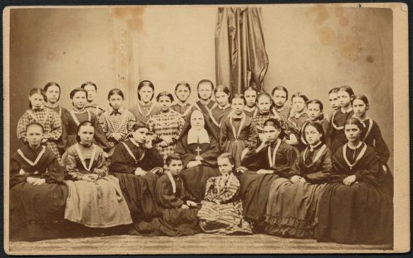 Portrait noir et blanc de 27 jeunes filles, médaille au cou, assises autour d'une religieuse.
