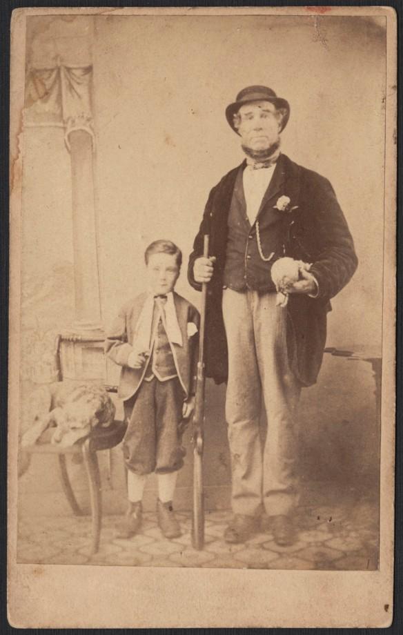 Photo noir et blanc montrant un homme, fusil à la main, debout aux côtés d'un garçon; près d'eux, un chien est couché sur une chaise.