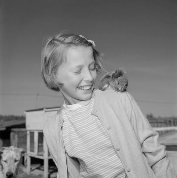 Photographie noir et blanc d'une jeune fille avec un écureuil sur son épaule gauche.