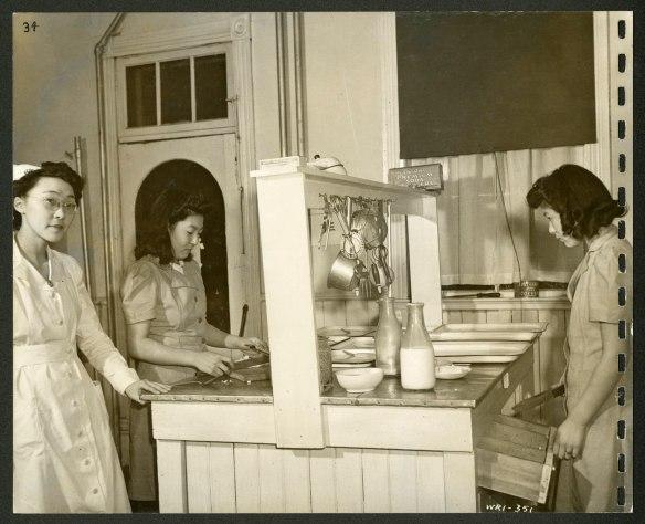 Trois femmes, dont une infirmière, se tiennent debout autour d'un îlot de cuisine sur lequel se trouvent des plateaux, de la vaisselle et des bouteilles de lait, et au centre duquel sont accrochés des ustensiles.