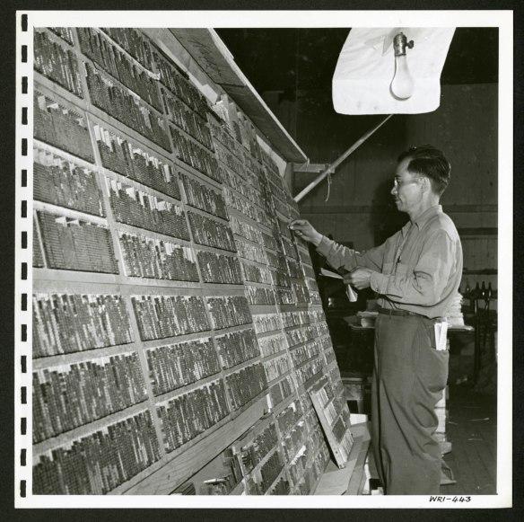 Un homme debout devant une grande étagère inclinée remplie de caractères japonais utilisés dans une presse à imprimer.
