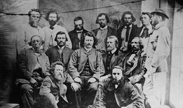 Une photographie noir et blanc de 14 hommes disposés en trois rangées (assis dans les deux premières et debout dans la dernière). Louis Riel est assis au centre.