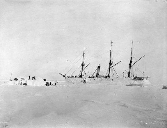 Photographie noir et blanc d'un bateau entouré de neige et de glace, avec des gens construisant un abri de neige à proximité.