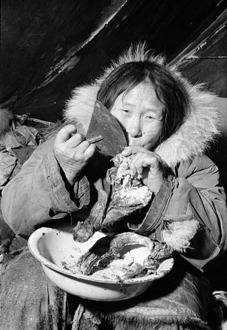Photo noir et blanc d'une femme inuk se servant de son ulu pour trancher de la viande.