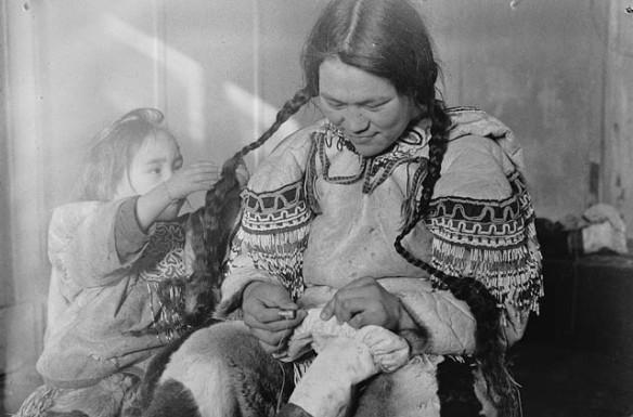 Photo noir et blanc d'une femme cousant des bottes en peau, alors qu'une enfant joue avec ses tresses.
