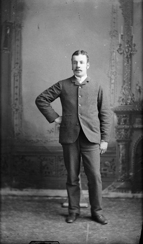 Portrait noir et blanc d'un homme debout dans un studio de photographie.