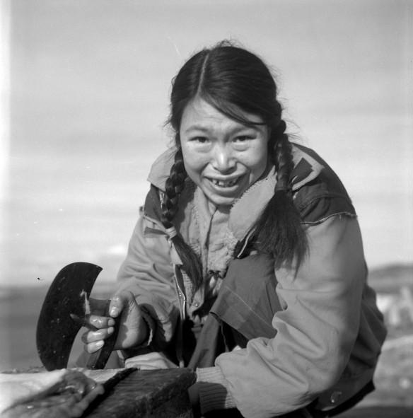 Photo noir et blanc d'une femme inuk se servant d'un ulu.