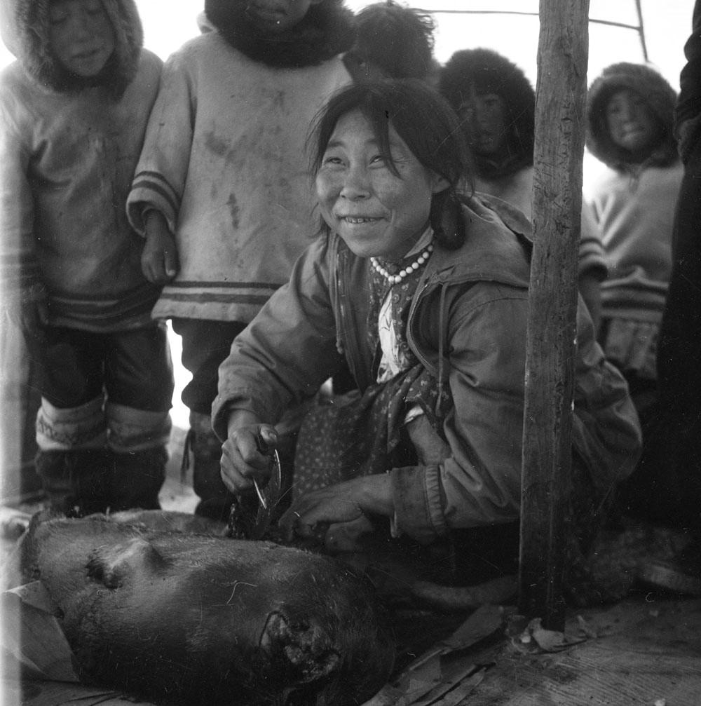 Photo noir et blanc d'une femme inuk se servant de son ulu.