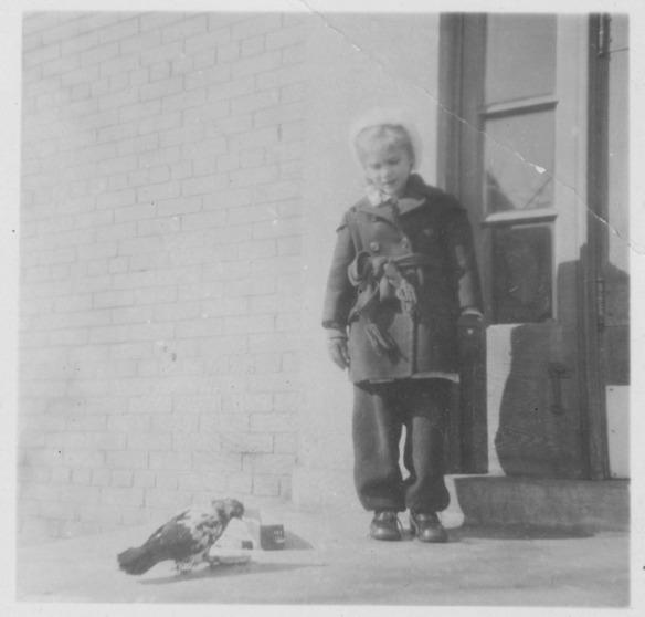 Photographie noir et blanc d'une petite fille (Ann MacDonald) debout près d'une porte. Elle regarde un pigeon sur le trottoir.