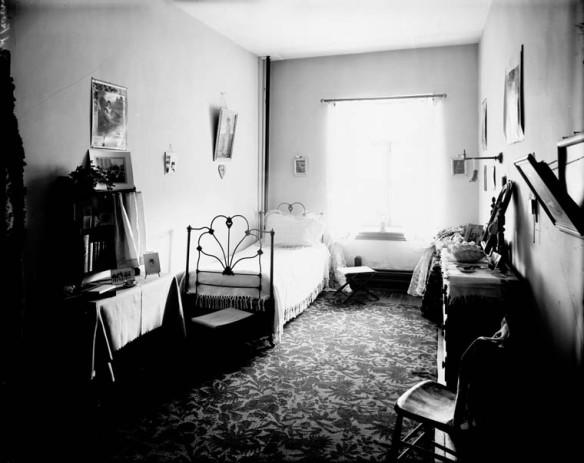 Photo noir et blanc d'un lit simple et de mobilier au collège pour femmes Coligny, à Ottawa.