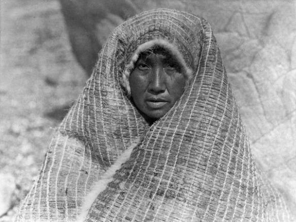 Photographie en noir et blanc d'une femme, drapée d'une couverture d'écorce, dont on ne voit que le visage.