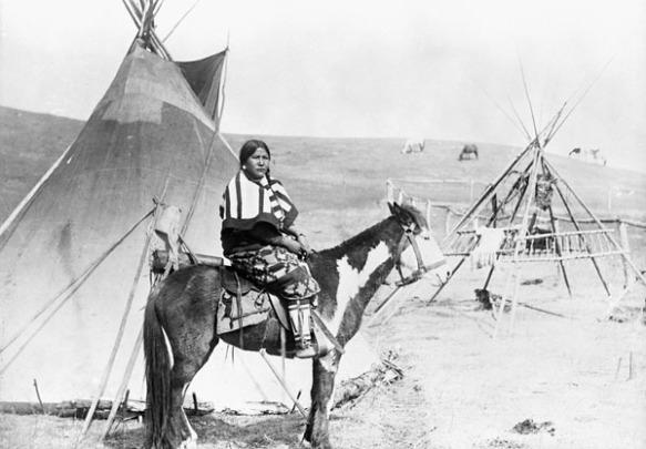 Photographie en noir et blanc d'une femme des Premières Nations à cheval devant un tipi.