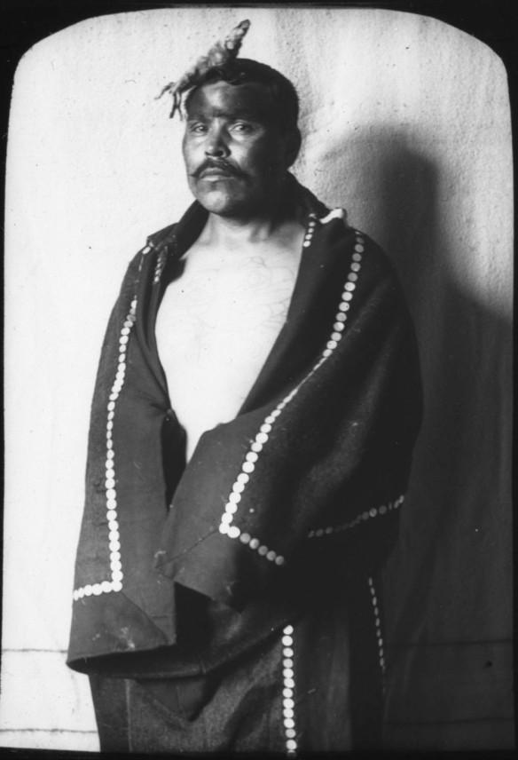 Photographie en noir et blanc d'un homme des Premières Nations enveloppé dans une couverture à boutons et portant une parure de tête.