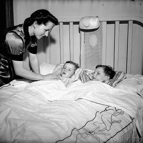Photo noir et blanc d'une mère bordant ses deux fils.