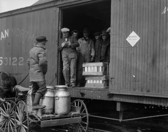 Photo noir et blanc d'un fermier près d'un train, avec des bidons de sirop d'érable sur sa charrette. Un homme tenant une planche à pince fait l'inventaire des bidons avant leur chargement.