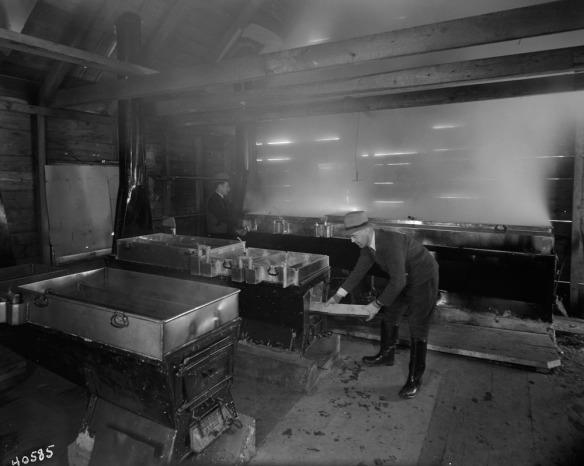 Photo noir et blanc de deux hommes à l'intérieur d'une cabane en bois rond, faisant bouillir de l'eau d'érable dans des cuves métalliques en forme d'auge.