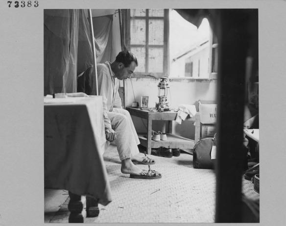 Photo noir et blanc d'un homme mettant ses pantoufles avant de se lever de son lit.