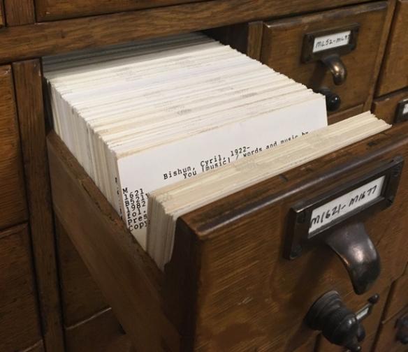 Catalogue sur fiches en bois brun, dont l'un des tiroirs est ouvert. Le tiroir contient plusieurs fiches catalographiques. Sur l'une d'elles, on peut lire le nom et l'année de naissance d'un auteur (Bishun, Cyril, 1922–).
