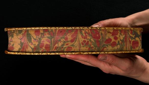 Photo couleur en gros plan montrant des mains qui tiennent un livre somptueusement décoré.