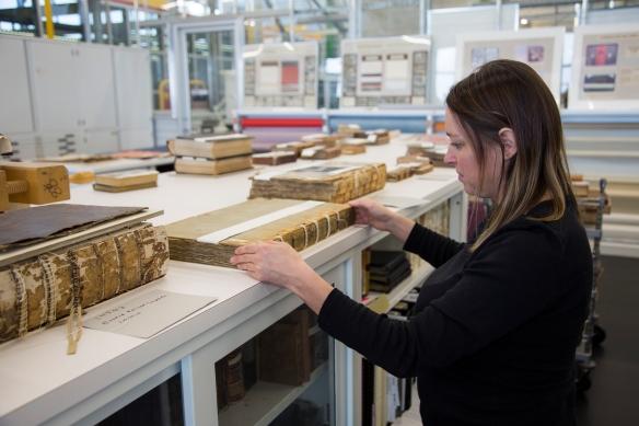 Photo couleur d'une personne se tenant debout devant une table dans le laboratoire de restauration des livres, réparant le dos d'un volume.