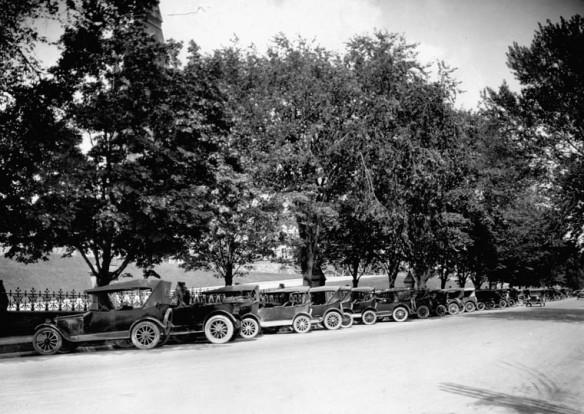 Photographie noir et blanc d'une rue bordée d'arbres avec une longue rangée d'autos stationnées de biais le long du trottoir.