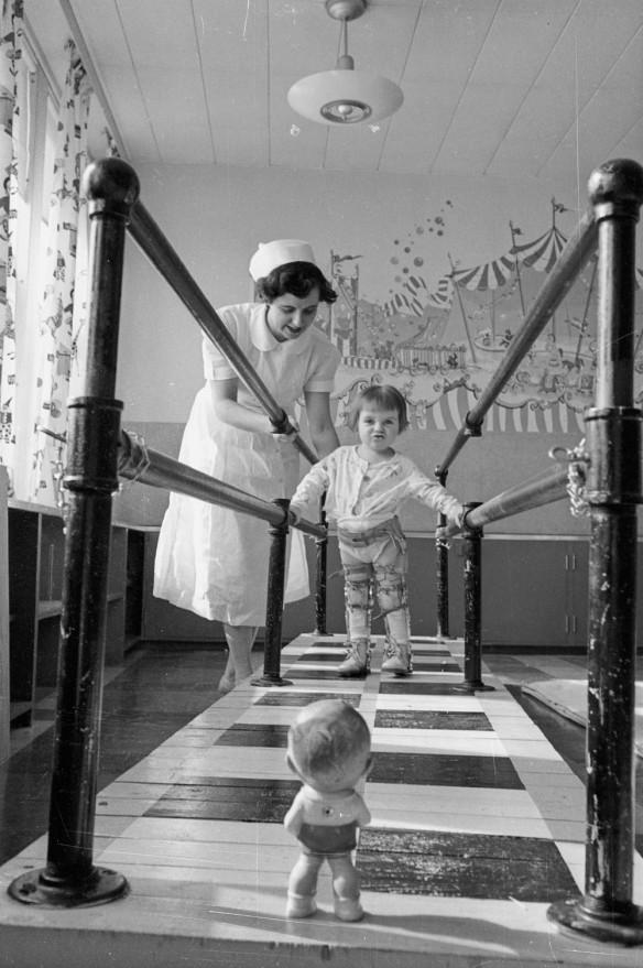 Photographie noir et blanc d'une femme aidant un jeune enfant portant des orthèses aux jambes à marcher en se tenant à des barres parallèles. Une petite poupée est placée à l'extrémité du parcours pour motiver l'enfant.