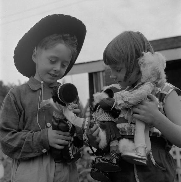 Photographie noir et blanc d'un garçon et d'une fille tenant et examinant trois poupées.