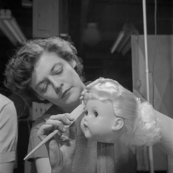 Photographie noir et blanc d'une femme brossant les cheveux d'une poupée. La tête de la poupée est montée sur un piquet de bois.