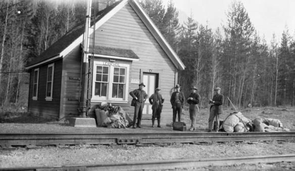 Photo noir et blanc de cinq hommes avec leurs bagages, debout à l'extérieur d'une petite gare du Chemin de fer Canadien Pacifique, Leanchoil (Colombie-Britannique)