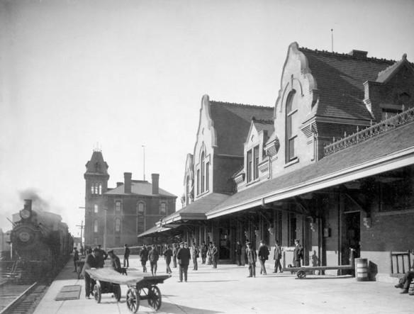 Photo noir et blanc de l'extérieur d'une gare du Chemin de fer Intercolonial; un train est arrêté sur la gauche et un groupe de personnes se tient sur le quai, Pictou (Nouvelle-Écosse)