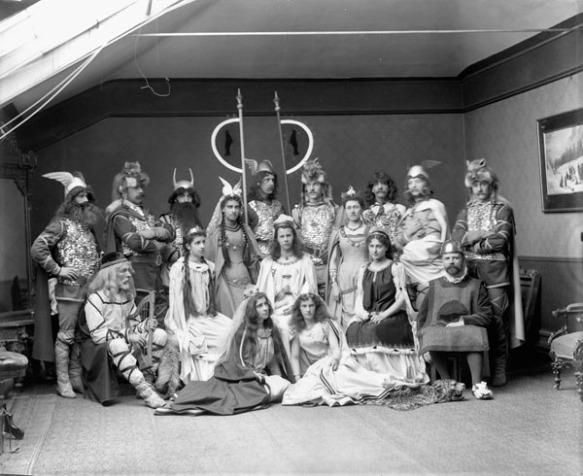Photo noir et blanc d'un groupe de dix-sept hommes, femmes et filles vêtus de costumes de Vikings dans un studio de photographie.