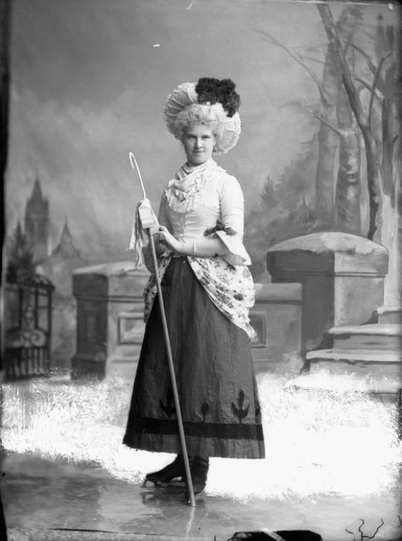 Photo noir et blanc d'une femme costumée en bergère chaussée de patins à glace dans un studio de photographie. L'arrière-plan est un paysage enneigé peint.