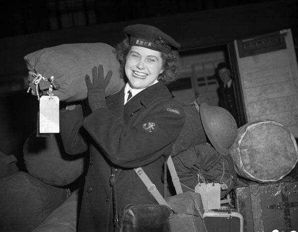 Photographie en noir et blanc d'une membre souriante du Service féminin de la Marine royale du Canada, qui transporte un gros sac sur son épaule.