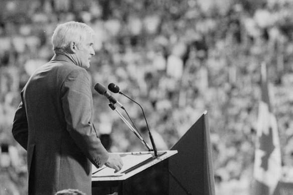 Photographie en noir et blanc montrant John Turner qui s'exprime au micro devant une foule. On peut apercevoir le drapeau du Canada.