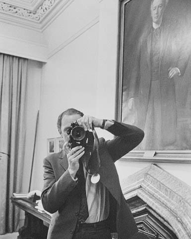 Photographie en noir et blanc du premier ministre Pierre Elliott Trudeau en train de prendre une photographie.