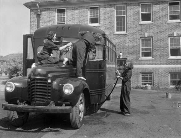 Photographie en noir et blanc de deux membres du Service féminin de la Marine royale du Canada qui lavent l'avant d'un autobus tandis que leur collègue en nettoie le côté avec un tuyau d'arrosage.
