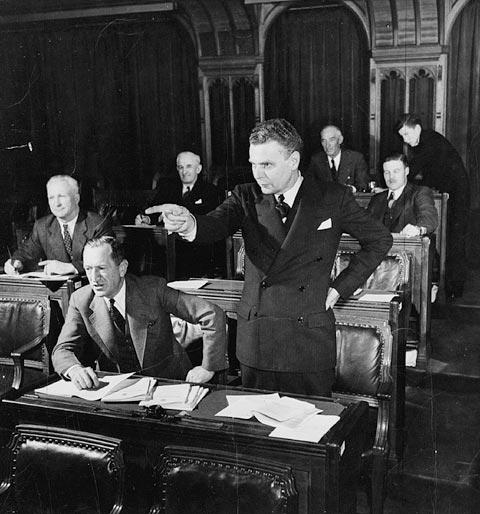 Photographie en noir et blanc qui montre le député John Diefenbaker, debout, s'adressant à la Chambre des communes. Autour de lui, on peut voir des députés assis à leurs pupitres.