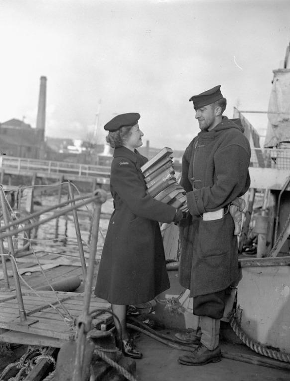 Photographie en noir et blanc d'une membre du Service féminin de la Marine royale du Canada remettant une pile de livres à un homme, à côté d'un navire.