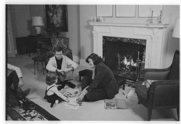 Photographie en noir et blanc sur laquelle on voit le premier ministre Joe Clark, son épouse et sa fille assis par terre dans le salon devant le foyer.
