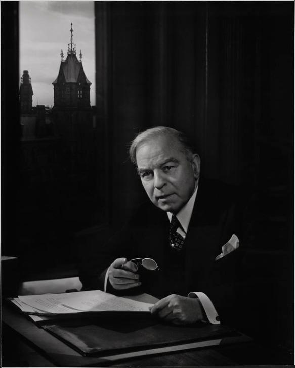 Photographie en noir et blanc montrant le premier ministre William Lyon Mackenzie King à son bureau. À l'arrière-plan, par une fenêtre, on aperçoit un des édifices du Parlement.