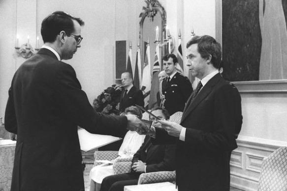 Photographie en noir et blanc de Joe Clark, debout, prêtant serment à titre de premier ministre du Canada. On peut voir à ses côtés, assis, le gouverneur général Edward Schreyer.