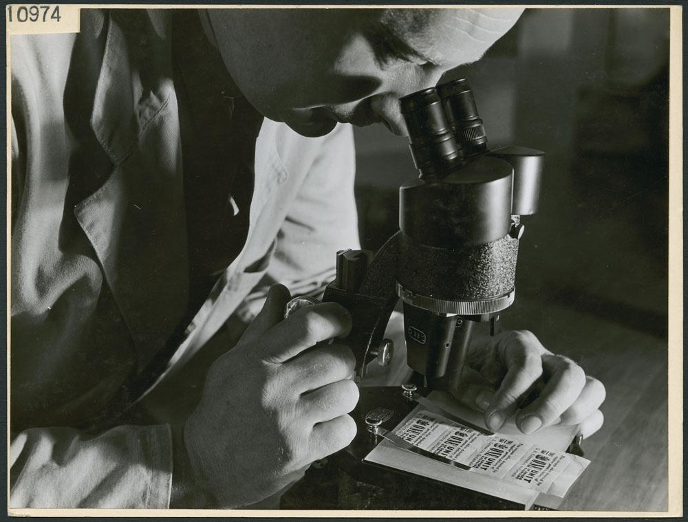 Photographie noir et blanc d'un homme observant à l'aide d'un microscope conçu pour détecter les billets, l'écriture et les coupons contrefaits.