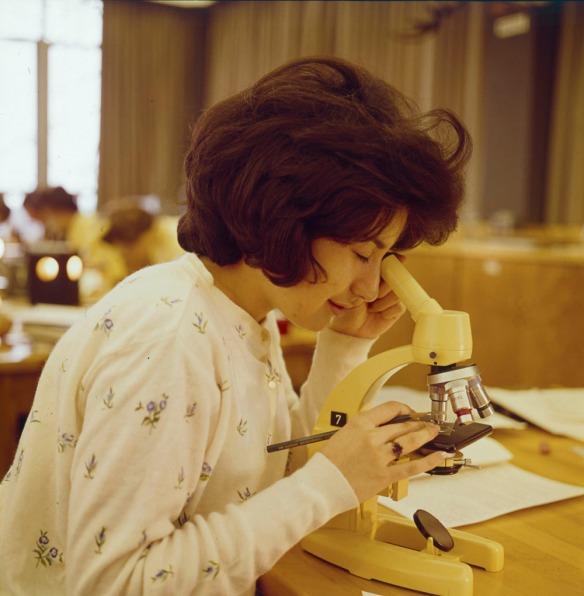 Photographie couleur d'une femme observant au microscope dans une salle de cours d'une université.