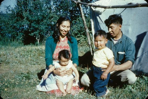 Un homme et une femme assis sur la pelouse avec deux jeunes enfants devant une tente en toile.